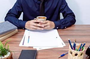 uomo d'affari che tiene una tazza di caffè in ufficio