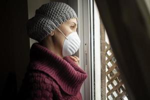 donna con maschere facciali al chiuso a casa, virus corona e concetto di quarantena