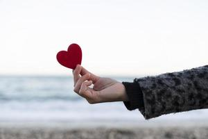 mano della donna che tiene un cuore rosso in riva al mare. concetto di San Valentino foto