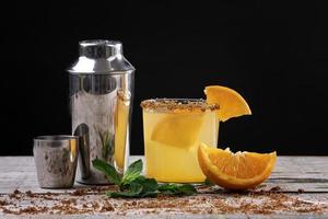 cocktail di succo d'arancia su base di legno decorata con uno shaker in metallo