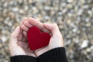 cuore rosso tra le mani di una donna su uno sfondo di sassi sulla spiaggia. concetto di san valentin foto
