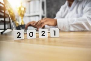 numero di cubo del 2021 sul tavolo in legno con uomo d'affari