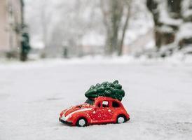 automobile rossa del giocattolo che trasporta un albero di natale