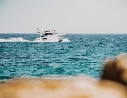 barca bianca e nera sul mare durante il giorno foto