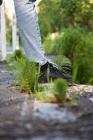 persona in jeans blu denim e scarpe nere in piedi sul percorso di cemento foto