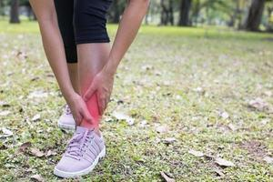 donna che tiene la sua caviglia nel dolore