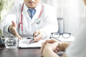 medico che spiega i moduli al paziente foto
