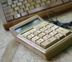 calcolatrice digitale e tastiera di bambù su legno foto