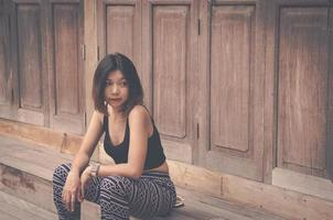 donna asiatica in posa da una parete in legno foto