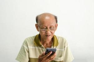 vecchio guardando il suo telefono cellulare foto