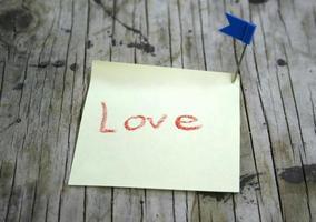 nota di carta su fondo in legno foto