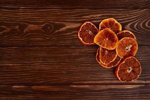 vista dall'alto di fette d'arancia essiccate disposte su sfondo di legno con spazio di copia foto