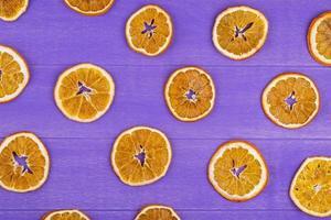 vista dall'alto di fette d'arancia essiccate isolato su fondo di legno viola foto