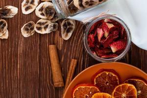 Vista dall'alto di chips di banana essiccate sparse da un barattolo di vetro e fette di fragola essiccate in un vasetto di vetro con fette di arancia essiccate su una piastra su sfondo di legno foto