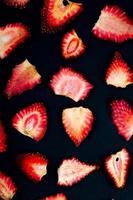 vista dall'alto di fette di fragole essiccate su sfondo nero foto