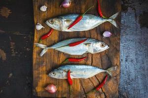 pesce sgombro sul tagliere di legno foto