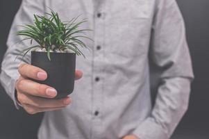 mano che tiene un vaso di fiori