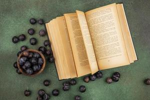 vista dall'alto delle piccole prugnole di frutta blu-nere acide su una ciotola di legno con prugnole isolate su uno sfondo verde foto