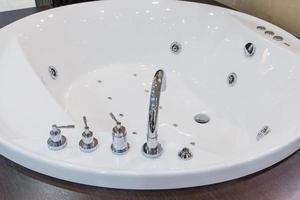rubinetto vasca in bagno moderno. vasca da bagno bianca con rubinetto e piastrelle beige. dettaglio del bagno, messa a fuoco selettiva