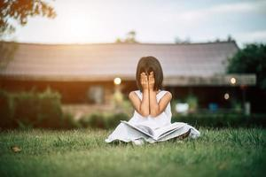 giovane ragazza che legge in giardino fuori casa sua foto
