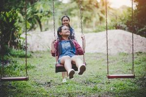due giovani ragazze seduti su un'altalena insieme foto