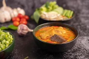 pollo al curry in una tazza nera con spaghetti di riso