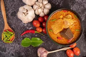 pollo al curry in una tazza nera foto