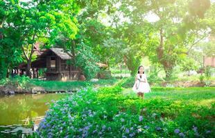 carina bambina asiatica in un abito bianco in piedi e con in mano una rosa rossa nel parco