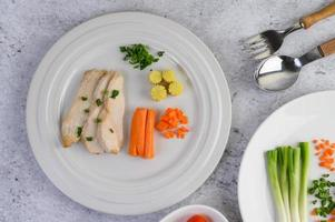 petto di pollo al vapore su un piatto bianco con cipolline e carote