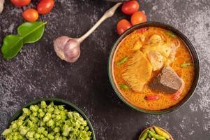 pollo al curry in una tazza nera con aglio e peperoni foto