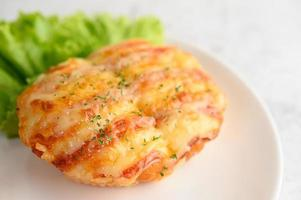 panino con salsiccia su un piatto bianco foto