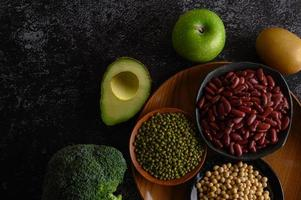 legumi e frutta su fondo scuro foto