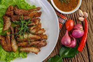 collo di maiale alla griglia su un piatto bianco con cipolla rossa, pomodoro e peperoncino su un tavolo di legno foto