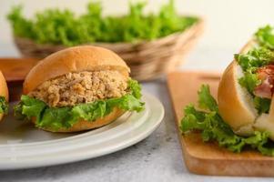 un hamburger posto magnificamente su un piatto bianco foto