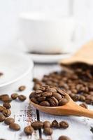 chicchi di caffè in un cucchiaio di legno e sacchi di canapa su un tavolo di legno bianco