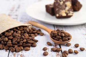 chicchi di caffè in un cucchiaio di legno e sacchi di canapa su un tavolo di legno bianco foto