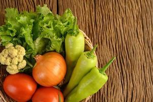 peperone, pomodoro, cipolla, insalata e cavolfiore su un cesto di legno su un tavolo di legno foto