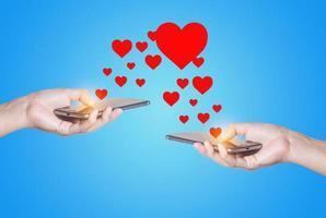 mani con telefono cellulare e cuori foto
