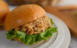 primo piano di hamburger posto sul piatto bianco magnificamente foto