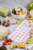 ingredienti della zuppa tra cui mais, funghi shiitake, pomodori, peperoncino e aglio foto
