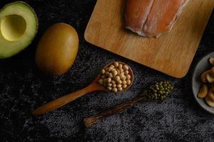 legumi, frutta e salmone su uno sfondo di cemento nero