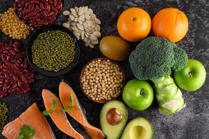 legumi, broccoli, frutta e salmone su uno sfondo di cemento nero foto