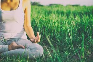 donna di yoga nella posizione del loto in un prato soleggiato foto