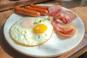 pancetta affumicata, uova fritte e salsiccia sul piatto bianco e tavolo in legno