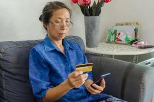 donna asiatica senior utilizzando una carta di credito per fare acquisti online
