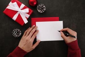 mani che scrivono mock-up biglietto di auguri foto