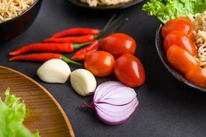 luminoso primo piano di fette di cipolla rossa, aglio, pomodoro e peperoni foto