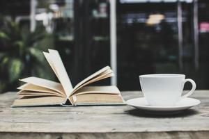 tazza di caffè e un libro aperto foto