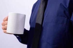 uomo che tiene una tazza bianca foto