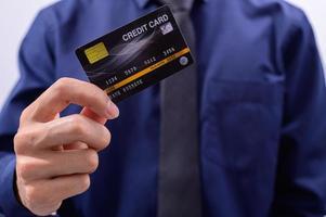 professionista in possesso di una carta di credito nera foto